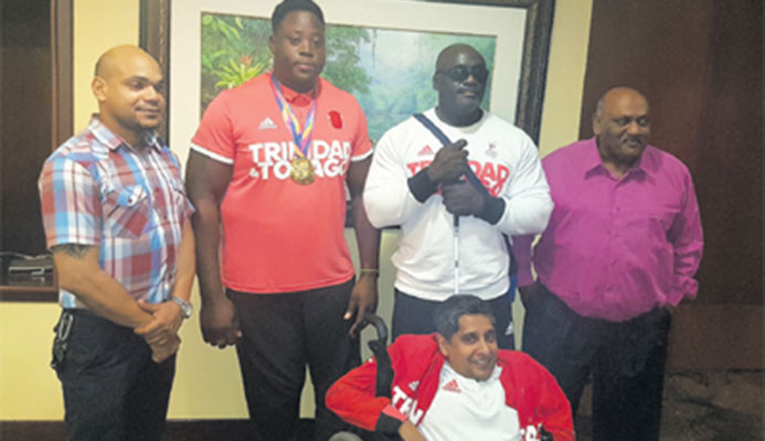 WELL DONE! Proud members of the T&T Paralympic Association, from second left: Akeem Stewart, Carlos Greene, Pradeep Vishnu and Sudhir Ramessar (front) at the VIP Lounge of the Piarco International Airport on Monday night with Ronson Hackshaw, the Assistant Director, Physical Education of the Ministry of Sports and Youth Affairs.