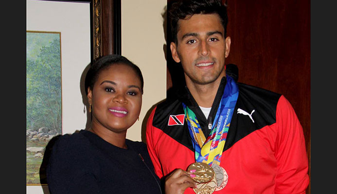Shamfa Cudjoe, Sports Minister (left) holds one of Dylan Carter's five medals that he earned at the CAC Games in Barranquilla, Colombia. Cudjoe met the TT swim team upon their return home at the VIP Lounge, Piarco International Airport yesterday.