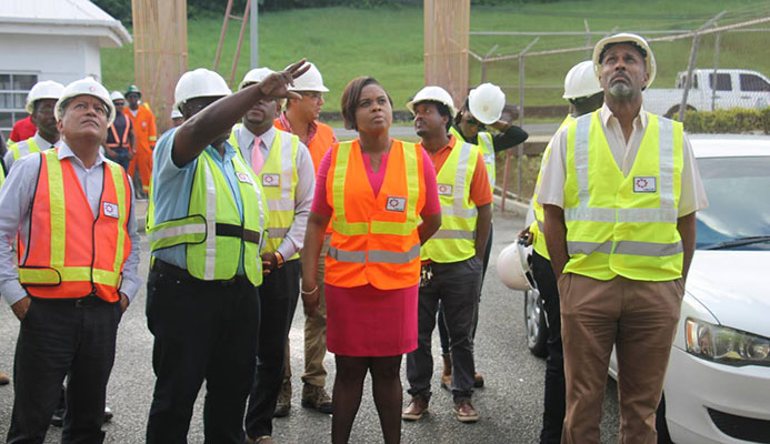 Project Manager Mc Jasse Salino points to the ongoing works at the Dwight Yorke Stadium, as Minister of Sport and Youth Affairs Shamfa Cudjoe (centre) and officials from THA, SPORTT and UDECOTT tour the facility on Tuesday.