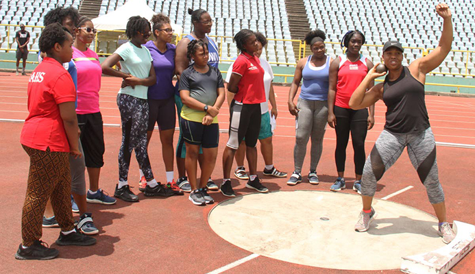 Four-time Olympian Cleopatra Borel,right, demonstrates shot put technique to participants at the Cleopatra Borel Foundation Throws Meet, yesterday, at the Hasely Crawford Stadium,Port of Spain.