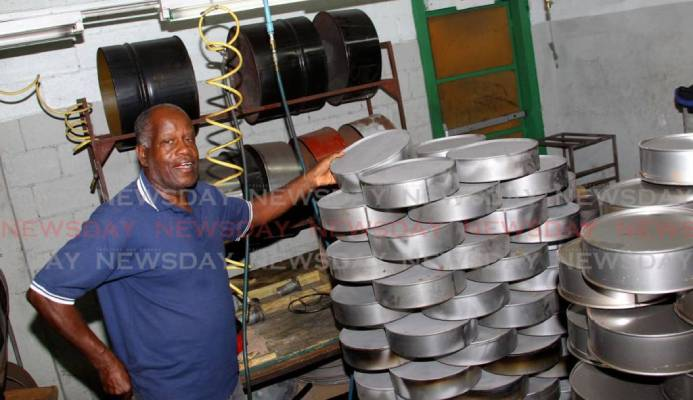 Panland president Michael Cooper highlights the miniature steelpans which the company manufacturers at its factory, Eastern Main Road, Laventille. - ROGER JACOB