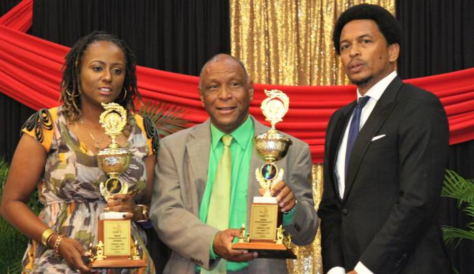 """Memphis Pioneers' Antonia Burton, left, and Cougars Athletics' Kelvin Nancoo, centre, with Trinidad and Tobago Olympic Committee president Brian Lewis after receiving the joint Champion Junior Club award on behalf of their clubs at the NAAA's 2019 Awards Function at the Radisson Hotel, Port-of-Spain, on Saturday evening. """