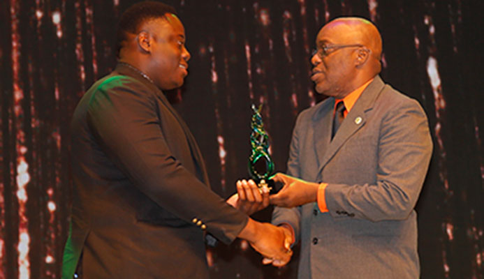 "TOP 10 NOMINEE Field athlete Akeem Stewart, left, is presented with his trophy by Kelvin Charles, Chief Secretary, Tobago House of Assembly, during the 2016 First Citizens Sports Foundation 2016 ""Sportwoman of the Year"" and ""Sportsman of the Year"" award function to be held at Queen's Hall, St Ann's on Friday night."