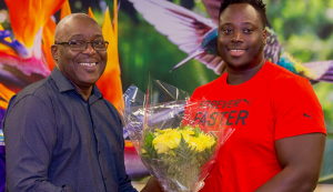 Chief Secretary Kelvin Charles presents 2019 Parapan Am double medallist Akeem Stewart with a bouquet of flowers at a ceremony to welcome him home on Tuesday at the ANR Robinson International Airport.